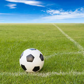 Soccer ball on soccer field against blue sky — Stock Photo