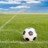 Soccer ball on soccer field against blue sky  — Stock Photo