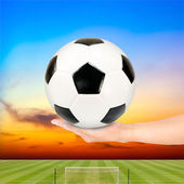 Soccer ball in hand with soccer field and sunset sky background — Stock Photo