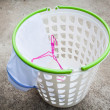 Empty white plastic laundry basket on the floor — Stock Photo