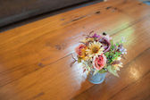 Beautiful colors of plastic flowers on wood table — Stock Photo