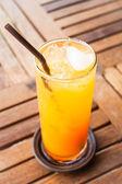 Fresh orange juice with heart ice cube — Stock Photo