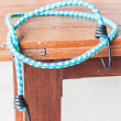 Black hooks of blue rubber band on wood table  — Stock Photo