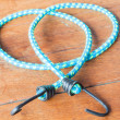 Stock Photo: Light blue rubber band with metal hooks