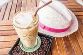 Kaltes glas eisgekühlter milch kaffee auf holztisch — Stockfoto