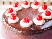 Chocolate whipped cream and red cherry on top — Stock Photo