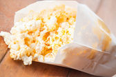 Popcorn packet opened with corn spilling out — Stock Photo