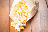 Popcorn paper bag opened with corn spilling out — Stock Photo