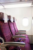 Airplane seat row in passenger cabin with window beside — Stock Photo