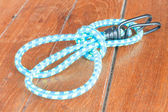 Light blue elastic rope on wood background — Stock Photo