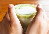 Ruce drží horký nápoj latte zelený čaj matcha — Stock fotografie