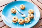 Smiling face of pineapple cookies on light blue dish — Stock fotografie