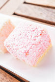 Pink lamington cakes up close on wood table — Stock Photo