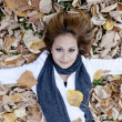 Smiling happy girl , lying in autumn leaves. Outdoor. - Stock Photo