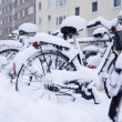 White snow covered bicycles - Stock Photo