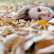Stock Photo: Smiling happy girl , lying in autumn leaves. Outdoor.