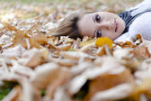 Smiling happy girl , lying in autumn leaves. Outdoor. — Stock Photo