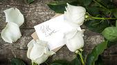 Rosas blancas con letra aislada en la mesa — Foto de Stock
