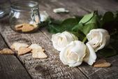 Three White Roses and Pastry on the Wooden Table — Stock Photo