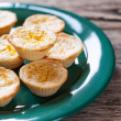 Lemon Tartlets on a green plate, wooden background — Stock Photo