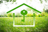 House and Key Symbols on a green summer landscape — Stock Photo