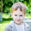 Happy Smiling Boy with blue eyes and fair hair in park — Stock Photo #29093871