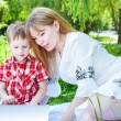Mother and Son reading a book in a park — Stock Photo