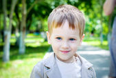 Happy Smiling Boy with blue eyes and fair hair in the park — Stock Photo