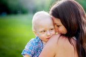 Joven madre y su pequeño hijo sobre un fondo de naturaleza — Foto de Stock