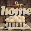 Eggs in Basket, Design Composition with word Home — Stock Photo #32498237