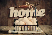 Eggs in the Basket, Design Composition with word Home — Stock Photo