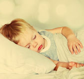 Boy Sleeping on a Bed. Toned — Stock Photo