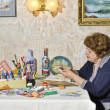 Happy elderly woman - artist makes decoupage — Стоковая фотография