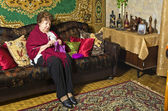 An elderly woman sitting on a couch and knits — Stock Photo