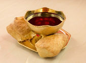 Golden chalice with red wine and bread broken into on a marble t — Stock Photo