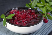 Lingonberry jam (cowberries) and branches with leaves — Stock Photo