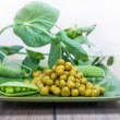 Boiled green peas, pods and branches — Stock Photo #50239677