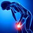 Female knee pain in blue - Stock Photo