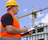 Male worker at Construction site with plan — Stock Photo