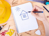 Drawing house and different tools on a wooden background — Stock Photo