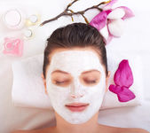 Chica joven y bella recibiendo máscara facial de rosa — Foto de Stock