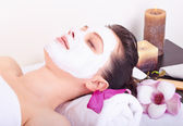 Beautiful girl receiving pink facial mask — Stock Photo