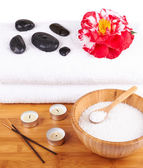 Spa setting with candles, flower, towel and stones — Stock Photo