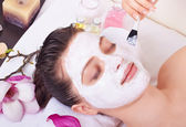 Beauty woman getting facial mask — Stock Photo