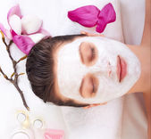 Young beautiful girl receiving pink facial mask — Stock Photo