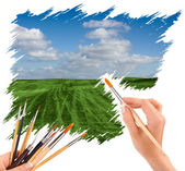 Hand with panit brush painting a beautiful summer landscape — Stock Photo