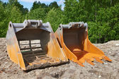 Excavator buckets on crushed stone — Stock Photo