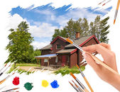 Hand with a brush painting of house with blue sky — Stock Photo
