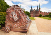Lion statue and Holstein Gate at Lubeck. Germany  — ストック写真