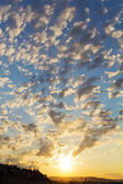 Sunset with cotton wool clouds — Stock Photo